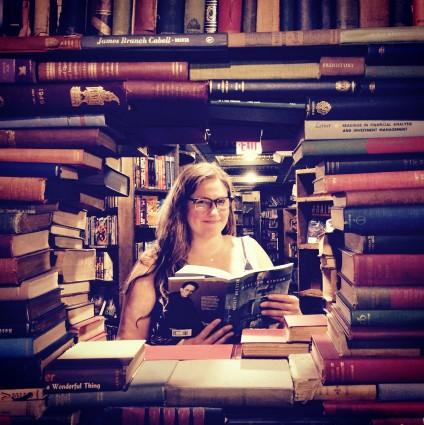 Instructor Karen Zgoda surrounded by stacks of books