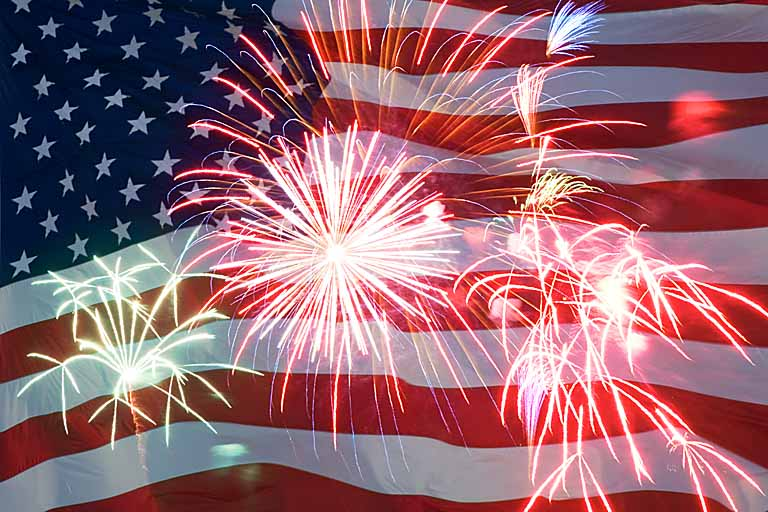 An American flag with fireworks in front of it, shows 4th of July celebration.