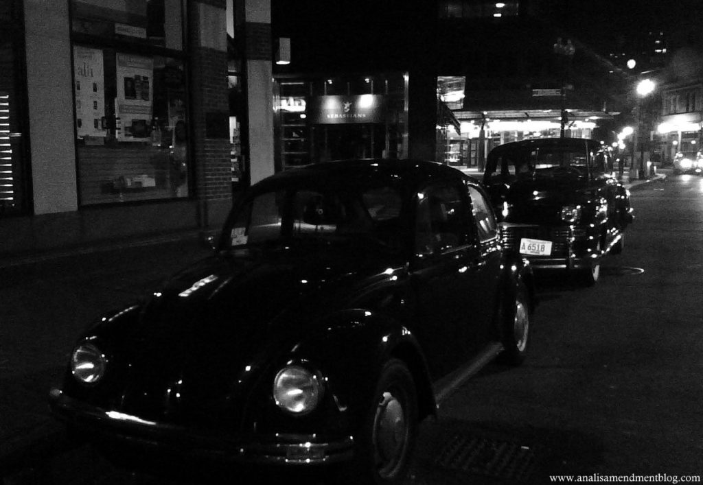 Black and white photo of antique cars on a Boston street at night.