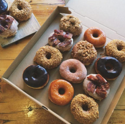 A picture of a dozen different flavored Union Square Donuts in a box.
