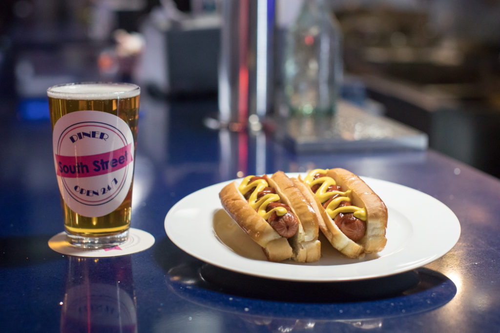 Glass of beer next to plate with two hot dogs topped with mustard in buns.
