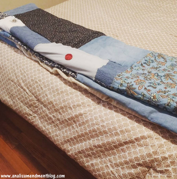 Folded patchwork quilt on top of bed spread.