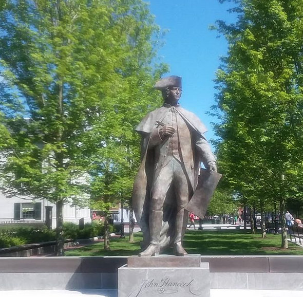 Image of John Hancock statue, represents the 4th of July.